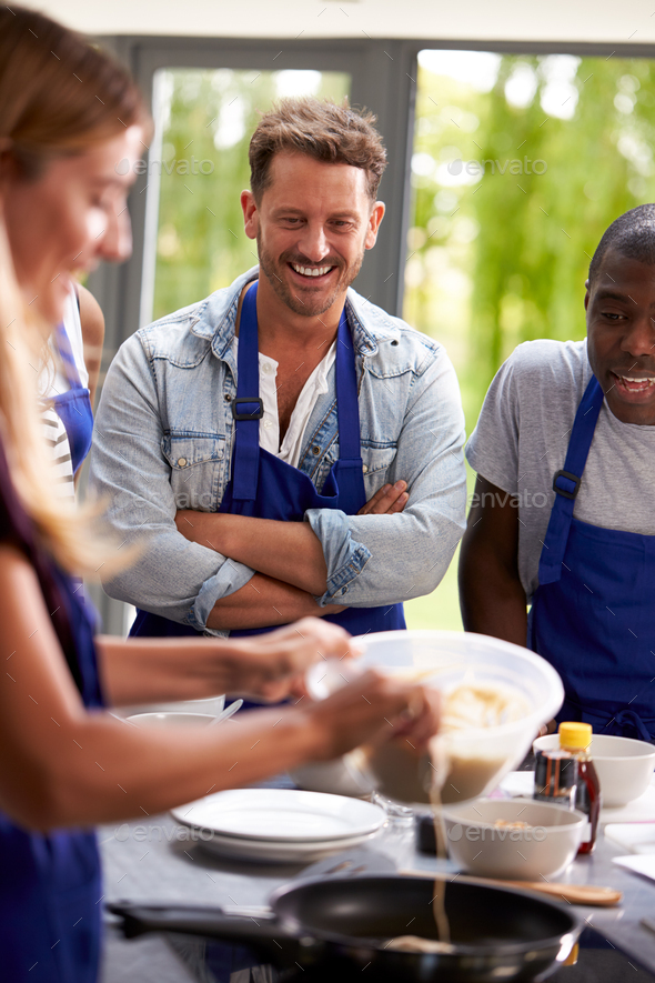 Students Watching Female Teacher Pouring Mixture Into Pan In Cookery Class - Stock Photo - Images