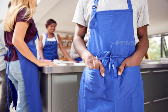 Close Up Of Man With Hands In Apron Pocket Taking Part In Cookery Class In Kitchen - Stock Photo - Images