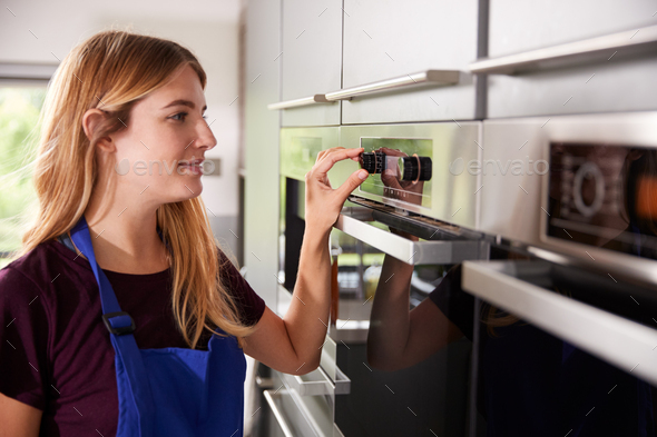 Woman Wearing Apron Setting Temperature Control On Oven In Kitchen - Stock Photo - Images