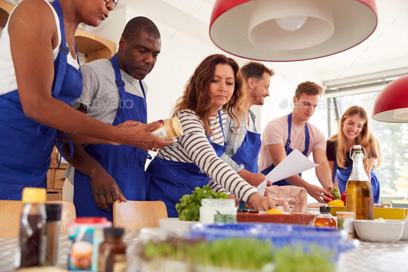 Male And Female Adult Students Looking At Recipe In Cookery Class In Kitchen - Stock Photo - Images