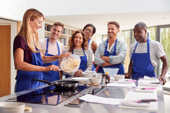 Female Teacher Making Pancake On Cooker In Cookery Class As Adult Students Look On - Stock Photo - Images