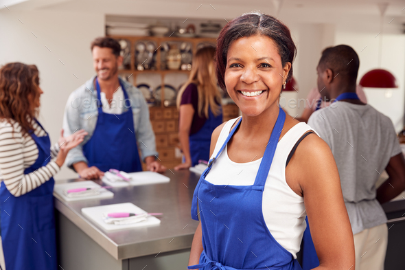 Portrait Of Smiling Mature Woman Wearing Apron Taking Part In Cookery Class In Kitchen - Stock Photo - Images