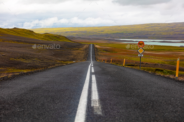 Road marking on highway by sign against sky - Stock Photo - Images