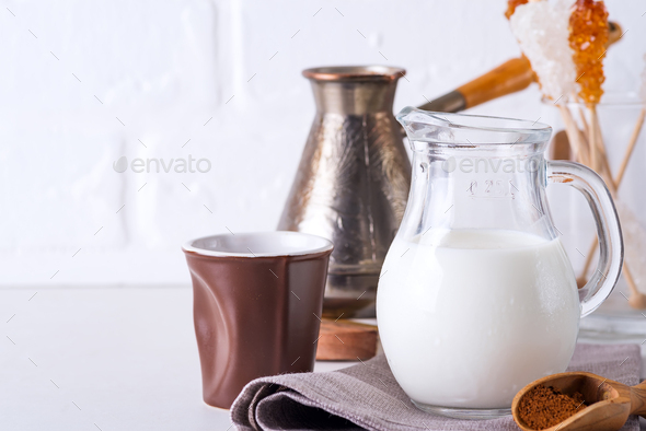Jug of milk and ground coffee for making a drink at home on a stone countertop against a white - Stock Photo - Images