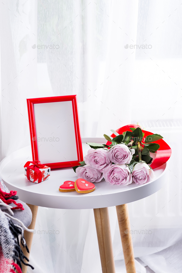 Homemade Valentines day heart cookies, pink roses and red frame on white table near window, copy - Stock Photo - Images