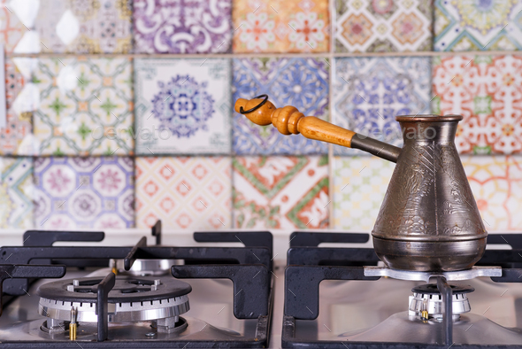Cooking coffee on a gas stove. Old turkish copper pot for brewing coffee on stove in the kitchen - Stock Photo - Images