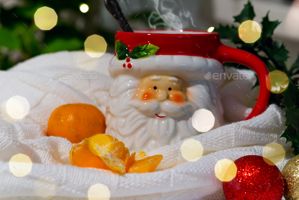 A cup in the form of Santa with hot tea and tangerines in a plaid with highlights on a background of - Stock Photo - Images