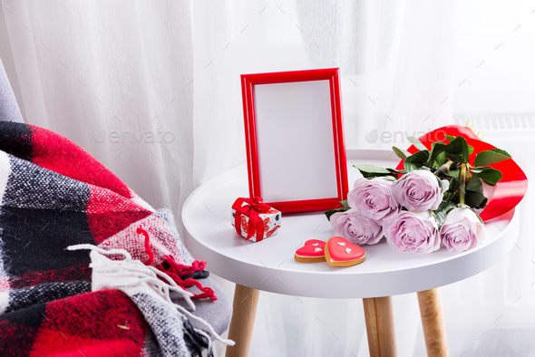 Homemade Valentines day heart cookies, pink roses and red frame on white table with chair and red - Stock Photo - Images