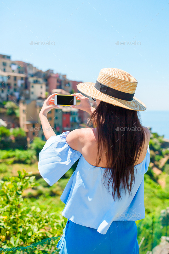 Young woman take a photo of beautiful view at old village in Cinque Terre, Liguria, Italy. European - Stock Photo - Images