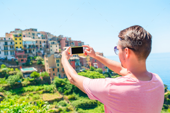 Young man taking selfie background beautiful old italian village, Cinque Terre, Liguria, Italy - Stock Photo - Images