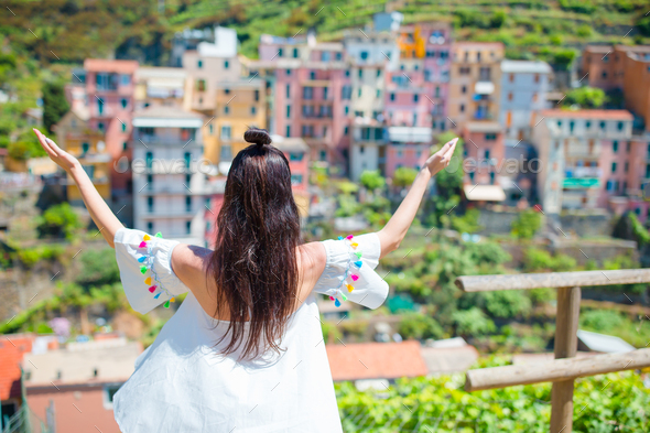 Back view of happy girl background beautiful view of Manarola, Cinque Terre, Liguria, Italy - Stock Photo - Images