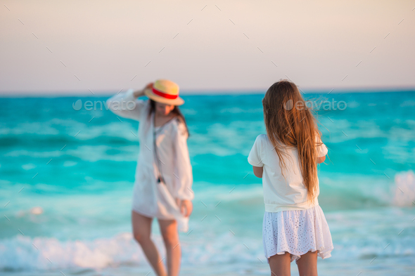 Little cute girl taking photo of her mom at tropical beach - Stock Photo - Images