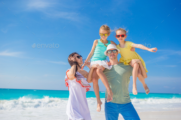 Portrait of happy beautiful family of four on a tropical beach on Carribean vacation - Stock Photo - Images