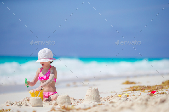 Adorable little girl playing with beach toys on white tropial beach - Stock Photo - Images