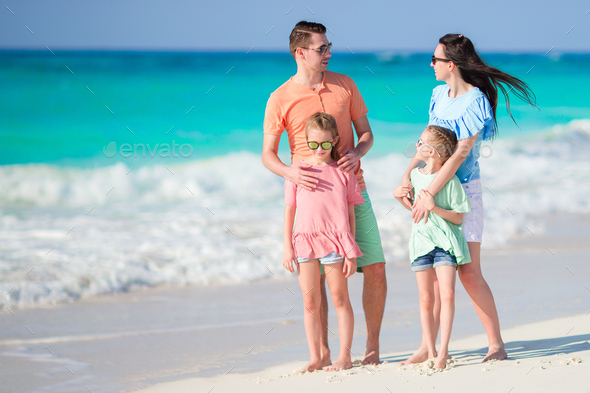 Happy beautiful family of four on a tropical beach - Stock Photo - Images