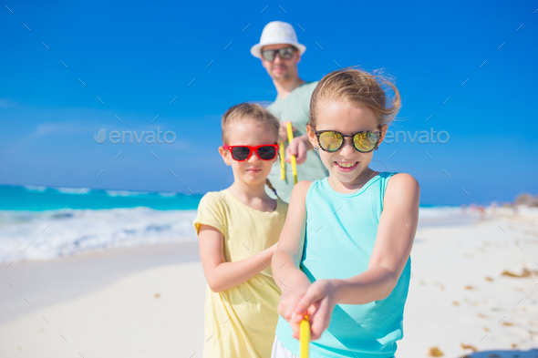 Family on white tropical beach have a lot of fun. Father and kids enjoy holidays on the seashore - Stock Photo - Images
