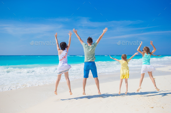 Happy beautiful family of four on a tropical beach. Parents and kids background seashore - Stock Photo - Images