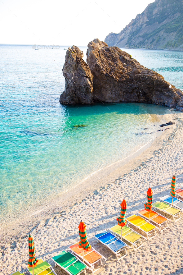Sunbeds and umbrellas at beautiful european seashore in Monterosso in Italy - Stock Photo - Images