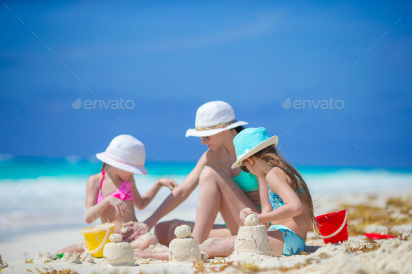 Family of mother and kids making sand castle at tropical beach - Stock Photo - Images