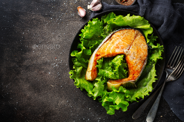 Closeup of baked salmon fish with green salad - Stock Photo - Images