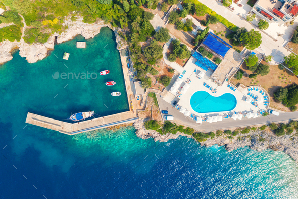 Aerial view of sea coast with clear blue water, boats and pool - Stock Photo - Images