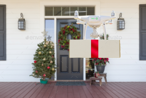 Drone Delivering Wrapped Package with Red Ribbon to Christmas Decorated House Porch - Stock Photo - Images