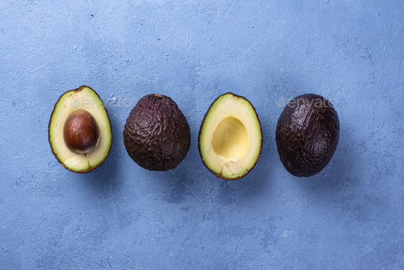 Half and whole avocado on blue background - Stock Photo - Images