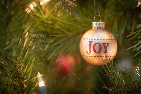 Joy Written on Christmas Ornament Hanging on Tree - Stock Photo - Images