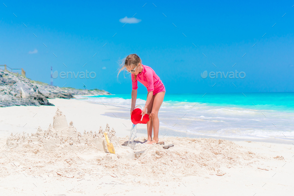 Little girls play with beach toys during tropical vacation - Stock Photo - Images