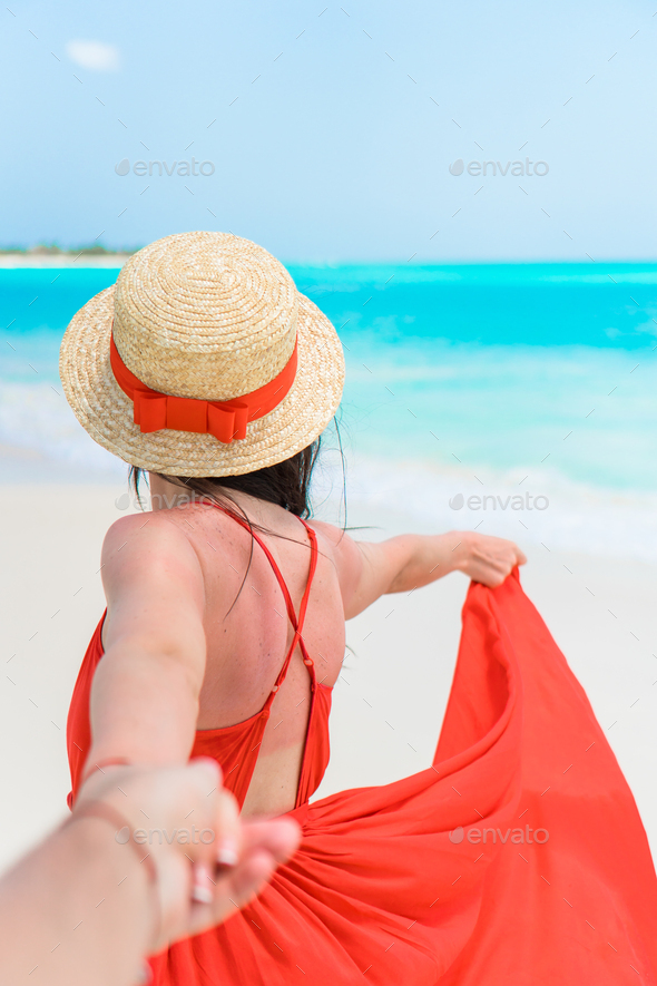 Young beautiful woman in hat on tropical seashore. Back view of young girl in red dress background - Stock Photo - Images