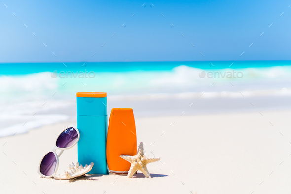 Suncream bottles, goggles, starfish and sunglasses on white sand beach background ocean - Stock Photo - Images