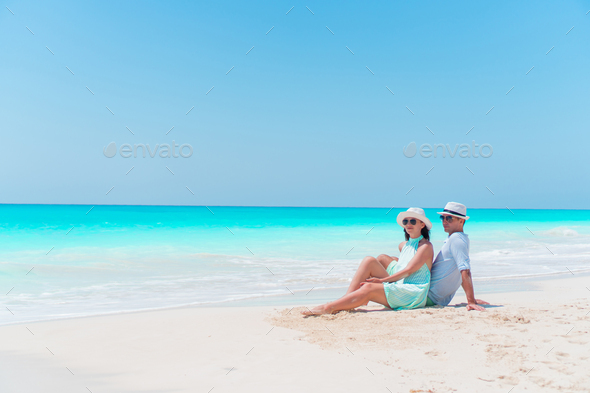 Young couple on white beach during summer vacation. Happy lovers enjoy their honeymoon - Stock Photo - Images