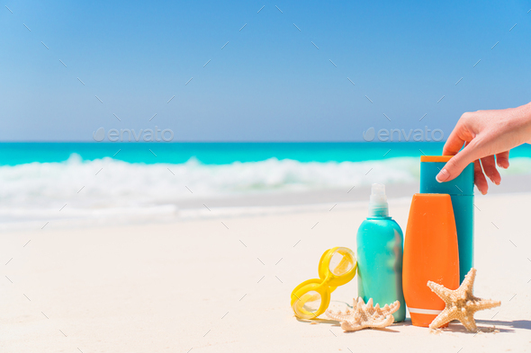Suncream bottles, goggles, starfish on white sand beach background ocean - Stock Photo - Images