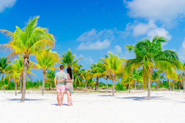 Young couple on white beach outdoors. Happy family enjoy their honeymoon in palm grove - Stock Photo - Images