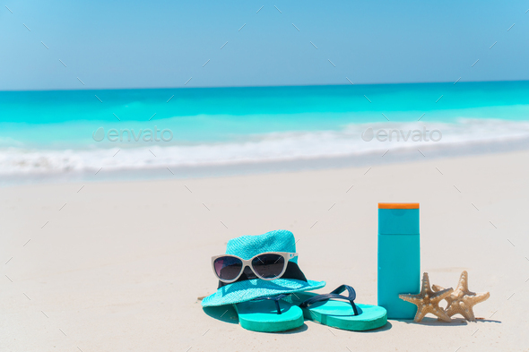 Beach accessories for sun protection. Suncream bottles, hat, sunglasses, flip flops on white sand - Stock Photo - Images
