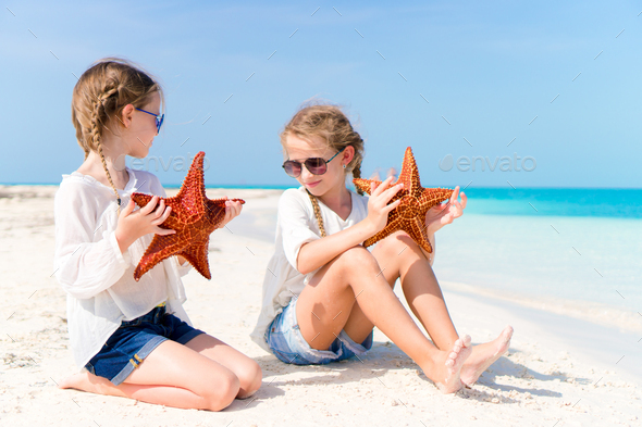 Adorable little girls with starfishes on white empty beach - Stock Photo - Images