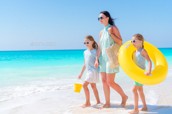 Adorable little girls and young mother on white beach. View to the family and ocean - Stock Photo - Images