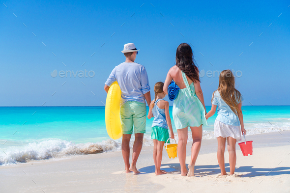 Family travel concept. Rear view of young family with two kids on the seashore - Stock Photo - Images