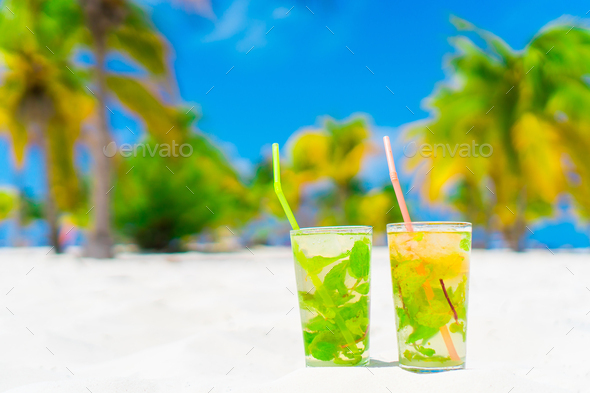Two cold tasty mohito cocktails on the white sandy beach in palm grove - Stock Photo - Images
