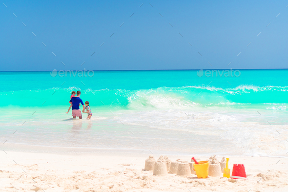 Sandcastle at white beach with plastic kids toys and sea background - Stock Photo - Images