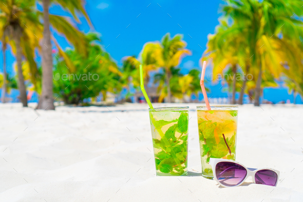 Two cold tasty mohito cocktails and white sunglasses on the white sandy beach - Stock Photo - Images