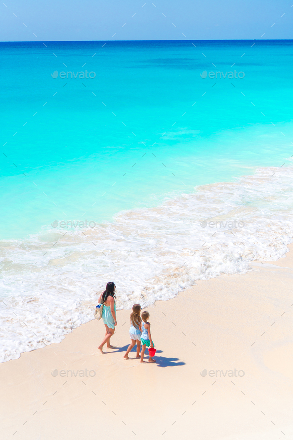Adorable little girls and young mother on white beach. View to the family and ocean from above - Stock Photo - Images