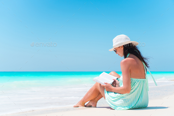 Young woman reading book on white sand beach - Stock Photo - Images