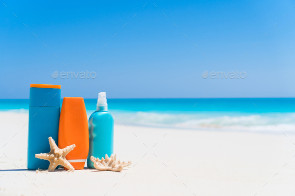Suncream bottles, goggles, starfish on white sand beach background ocean - Stock Photo - Images