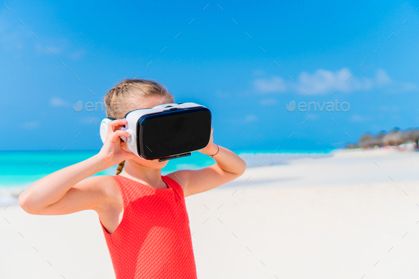 Cute little child girl using VR virtual reality goggles. Adorable girl look into the virtual glasses - Stock Photo - Images