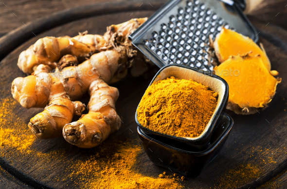 Turmeric powder and fresh turmeric - Stock Photo - Images
