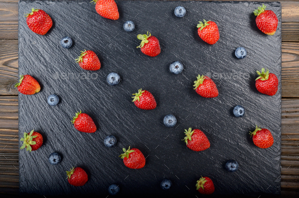 Flat lay view at ripe bilberry and strawberries on slate stone tray closeup - Stock Photo - Images