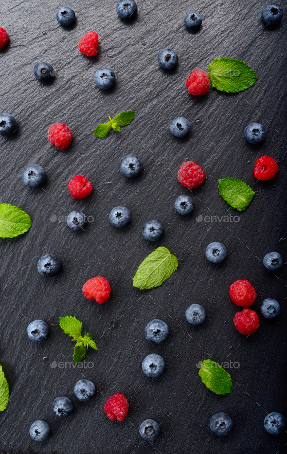 Flat lay view at ripe bilberry and raspberry berries on slate stone tray closeup - Stock Photo - Images