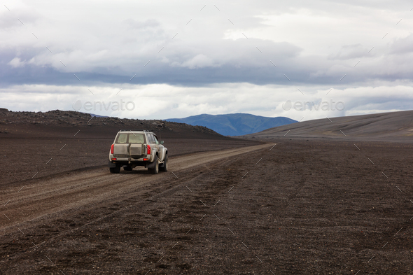 SUV on dirt road against cloudy sky - Stock Photo - Images