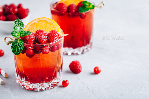 Raspberry Cranberry Sangria Punch or Mojito in glass with orange slices and mint - Stock Photo - Images